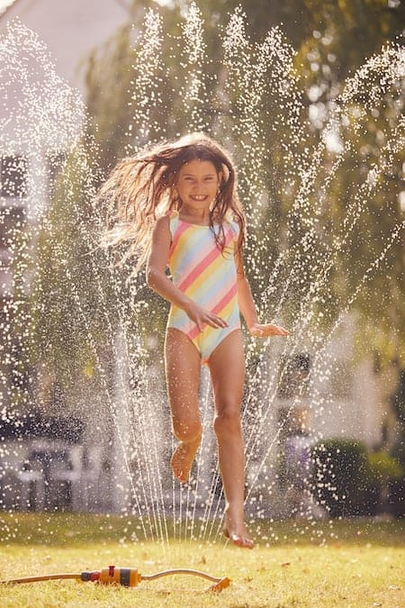 girl jumping over a sprinkler in a nursery rhyme activity for preschoolers