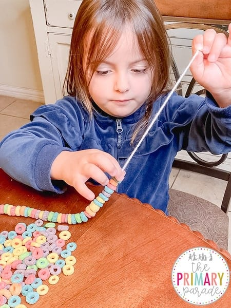St Patricks Day activities for preschool threading rainbow necklaces with Fruit Loops and string